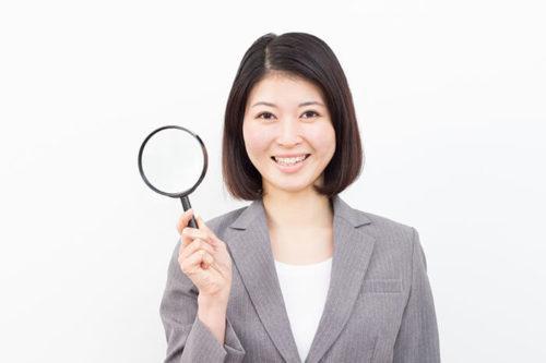 虫眼鏡を持つスーツ姿の女性